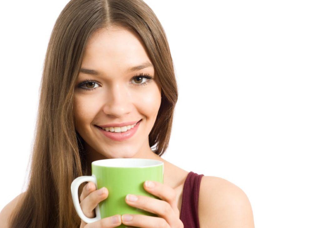 Chica con piel radiante y taza verde