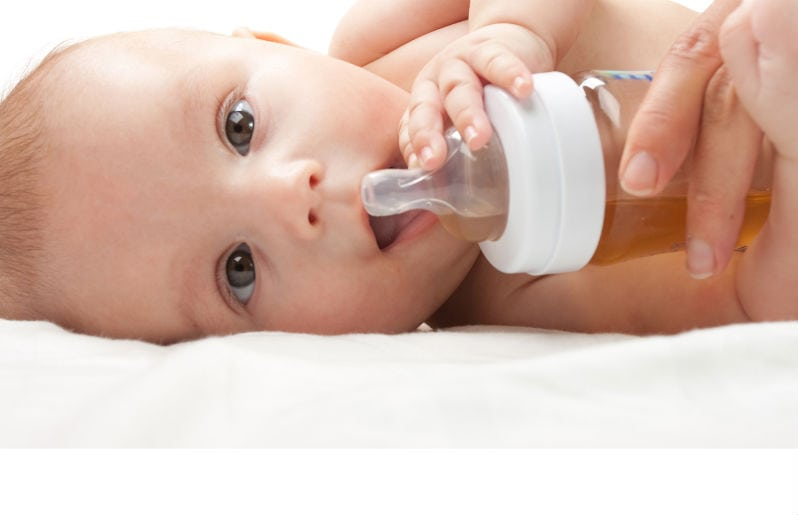 Bebé tomando té de manzanilla en su mamila