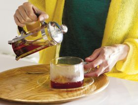 Mujer con artritis sirviéndose té