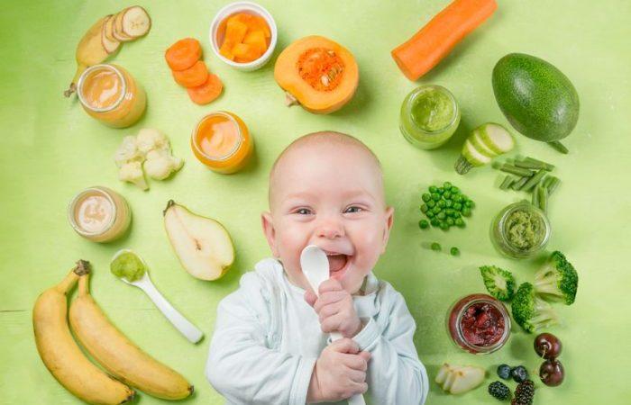 Bebé con alimentos verdes a su alrededor